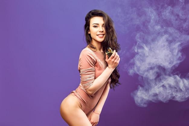 Donna calda in tuta in piedi e svapare sulla parete viola.