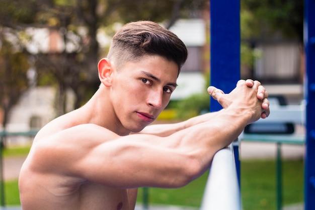 Caldo giovane uomo muscoloso che si allena in un parco giochi