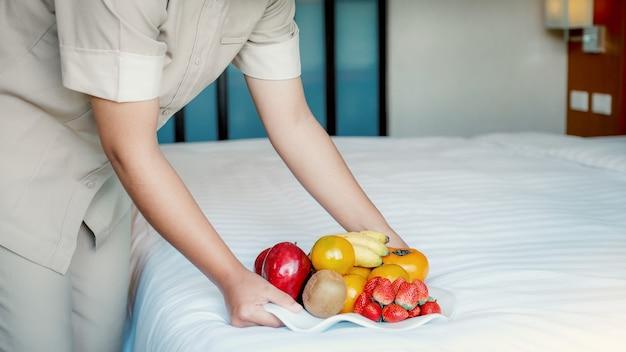 La mano della cameriera d'albergo che tiene la frutta si ferma nella camera da letto dell'hotel di lusso pronta per i viaggi turistici.