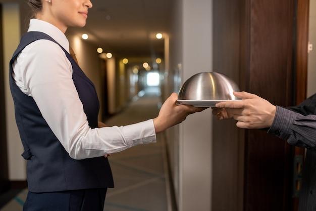 Direttore dell'hotel che passa il vassoio con il pranzo all'uomo d'affari