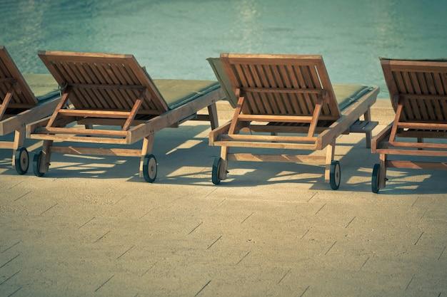 Sedie a bordo piscina dell'hotel con vista sulla piscina. scatto orizzontale in stile vintage