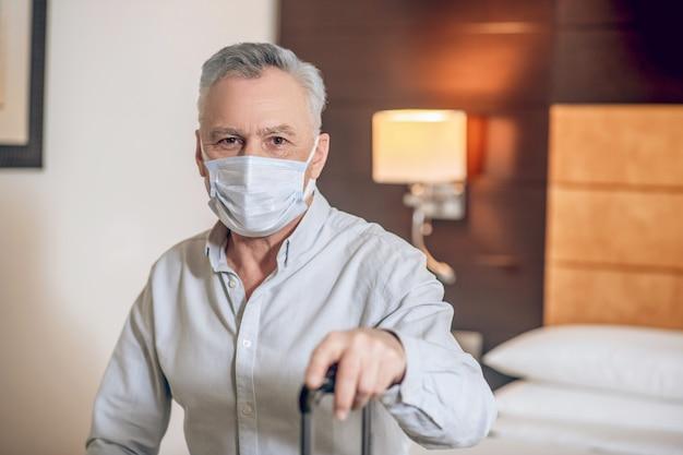 Nella stanza d'albergo. uomo di mezza età dai capelli grigi con una maschera protettiva in una stanza d'albergo