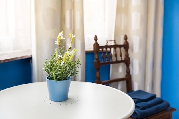 Interiore della camera d'albergo, fiori in vaso sul tavolo, turismo in europa. mobilia europea del motel, appartamento per svago comodo, nessuno