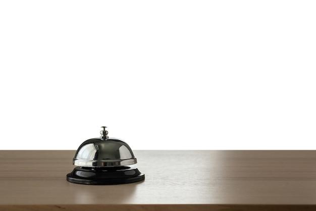 Campana di servizio dell'hotel sul contatore di legno isolato su priorità bassa bianca