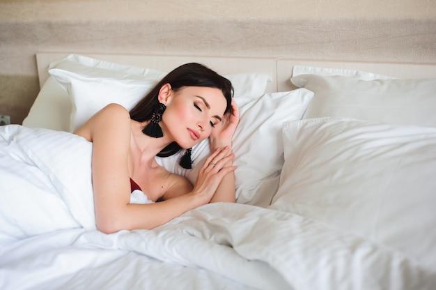 Concetto dell'hotel, di viaggio e di felicità - bella donna che dorme nel letto.