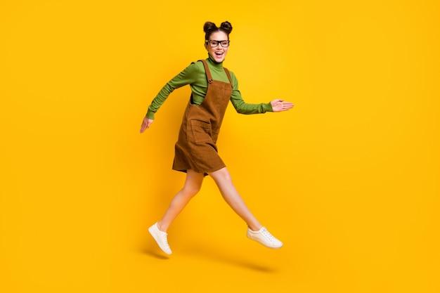 Foto di una ragazza allegra che salta in tuta su uno sfondo di colore giallo