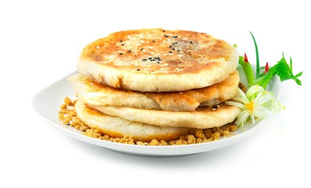 I pancake dolci coreani hotteok sono uno degli snack coreani più popolari del cibo di strada. ripieno a base di zucchero di canna, cannella e arachidi decora cipollotto e porro intagliato