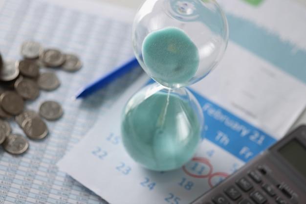 Il calendario e le monete della clessidra giacciono sulla pianificazione del bilancio familiare del tavolo per il concetto del mese