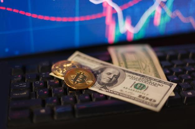 Clessidra, dollari e bitcoin sulla tastiera di un computer sullo sfondo dei grafici