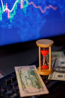Clessidra e dollari sulla tastiera sullo sfondo dei grafici