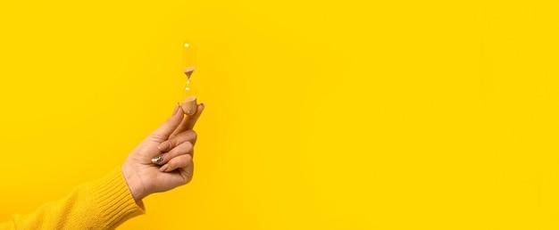 Clessidra in mano su sfondo giallo, moc-up panoramico con spazio per il testo