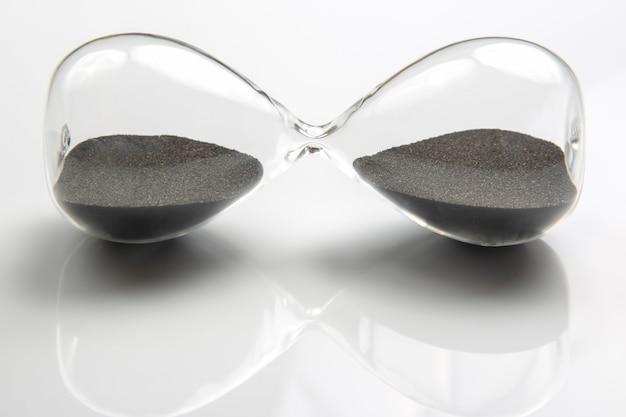Clessidra su una superficie chiara. il tempo è denaro. soluzioni aziendali in tempo.