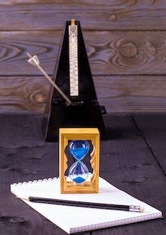 Clessidra, metronomo e blocco note con una matita