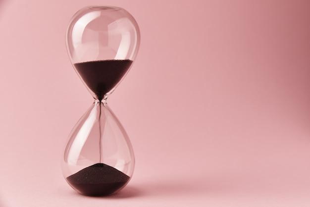 Clessidra su sfondo rosa, da vicino. urgenza e esaurimento del concetto di tempo