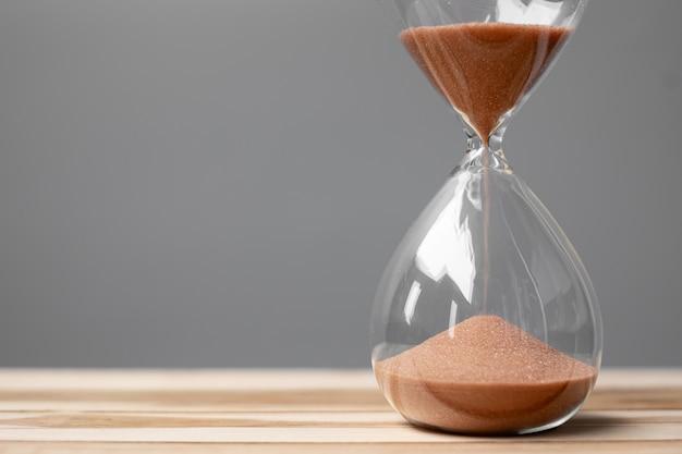 Clessidra sull'ufficio della tavola con lo spazio della copia, sabbia che scorre attraverso il bulbo di sandglass che misura il tempo che passa. conto alla rovescia, scadenza, tempo di vita e concetto di pensionamento