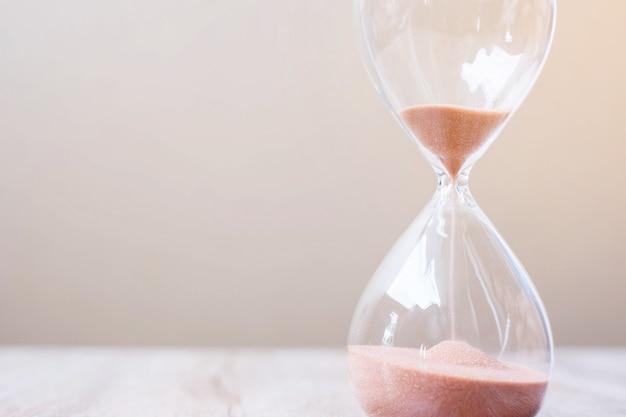 Clessidra sul tavolo, sabbia che scorre attraverso il bulbo di sandglass misurando il tempo che passa. conto alla rovescia, scadenza, durata della vita e concetto di pensionamento
