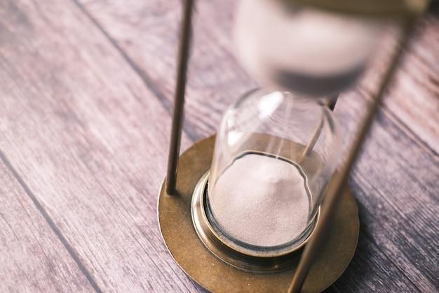 Clessidra sulla sabbia del tavolo che scorre attraverso il bulbo di clessidra