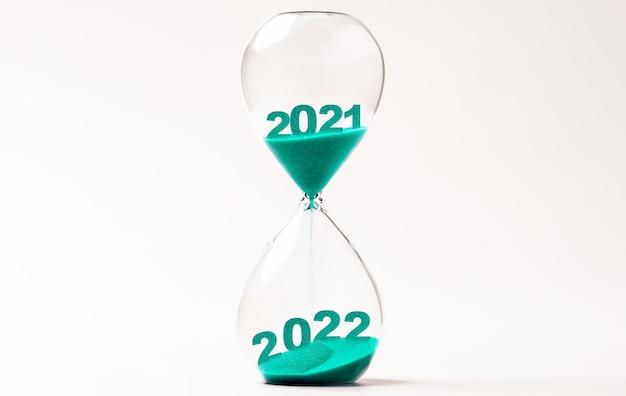 Clessidra con sabbia blu per il cambiamento dal 2021 al 2022 anno, conto alla rovescia e preparazione buon natale e felice anno nuovo concetto.
