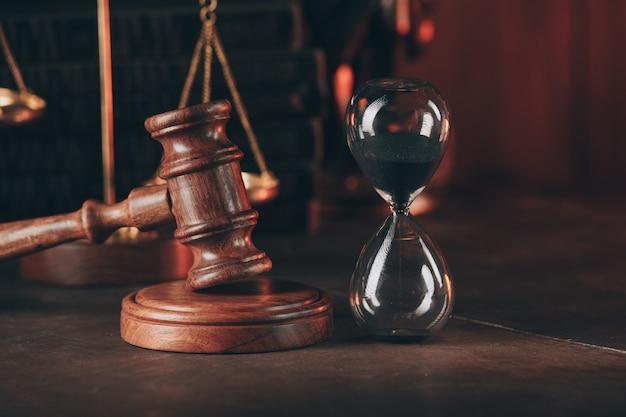 Martelletto del giudice a clessidra e legno sul primo piano del tavolo
