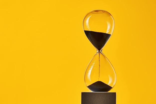 Clessidra su sfondo giallo con spazio di copia. concetto di rimanere a corto di tempo e scadenza