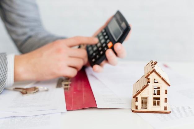 Agente immobiliare utilizzando la calcolatrice