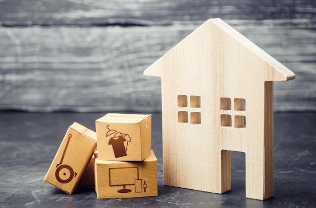 Casa e scatole con merce ordinata consegnata riorientamento dell'attività verso i servizi online e le vendite in rete