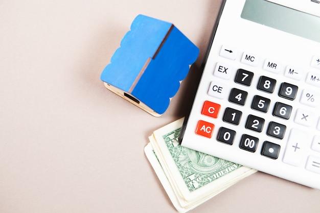 Casa, calcolatrice e soldi sul tavolo. il concetto di calcolo del costo della casa