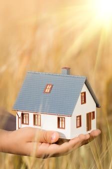 Casa nelle mani dei bambini su sfondo giallo autunnale concetto immobiliare