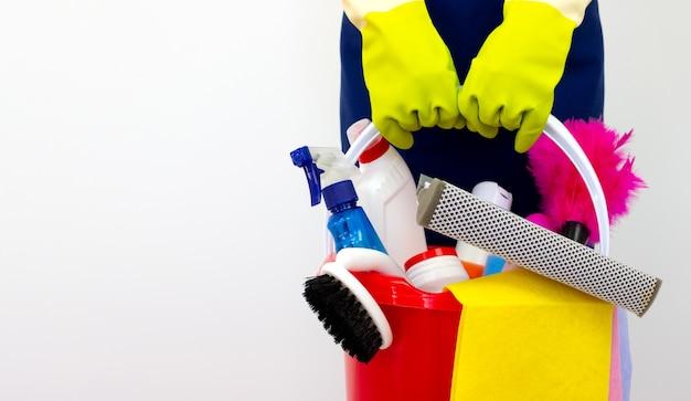 I prodotti per la pulizia della casa si accumulano in mano con guanti verdi su sfondo bianco. servizio di pulizia concettuale