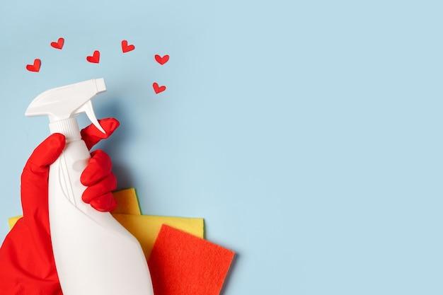 Spray per la pulizia della casa in mano femminile su sfondo blu con cuori rossi, copia dello spazio