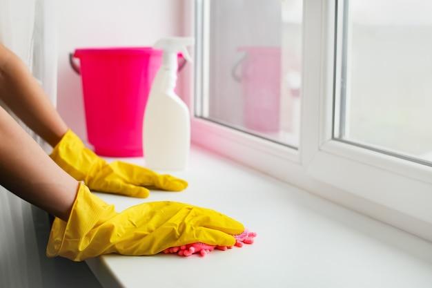 Pulizia della casa e lavaggio di finestre e davanzali, mano guantata lava il vetro