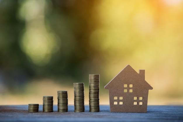 Casa e mucchio di monete concetto di mutuo per la casa denaro da finanza aziendale monete affari finanziari di successo risparmio per progetti immobiliari di piccolo modello