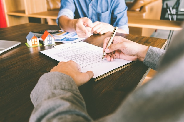 Contratto di casa, l'uomo firma un contratto per l'acquisto di una casa con un agente immobiliare