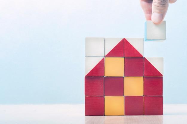 Casa dei cubi. su un quadrato di cubi, il mosaico presenta una casa. la mano mette l'ultimo dado nel mosaico. concetto di business di costruzione, successo aziendale, concetto di business.