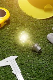 Concetto di idee di ingegnere e architetto di casa con lampadina. cappello giallo e strumenti su erba verde green