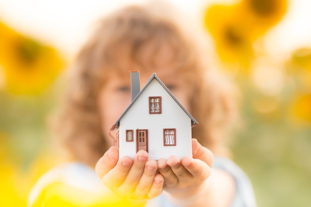Casa in mano su sfondo verde primaverile. concetto immobiliare