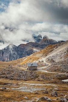 Casa sul sentiero nelle dolomiti con vista panoramica sulle montagne ricoperte di nuvole