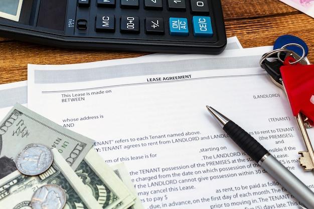 Casa, casa, proprietà, contratto di affitto contratto di locazione immobiliare penna denaro monete chiavi in legno da vicino
