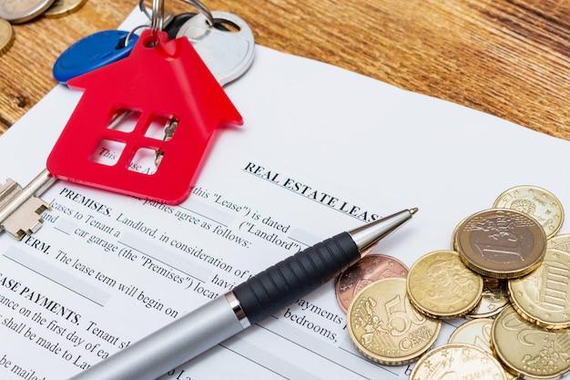 Casa, casa, proprietà, contratto di affitto contratto di locazione immobiliare penna denaro monete chiavi di legno