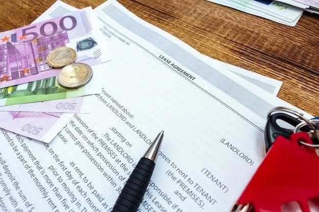Casa, casa, proprietà, contratto di locazione immobiliare, contratto di affitto con penna, denaro, monete, chiavi.