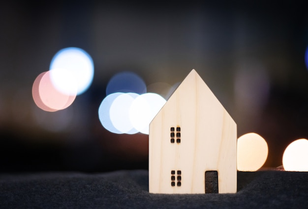 Modello di legno della casa o della casa per il concetto felice della famiglia con la luce del bokeh dalla città moderna del centro