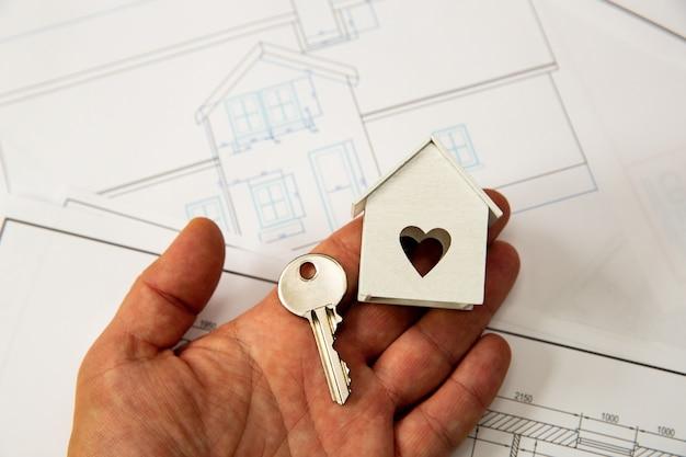 Casa e chiave sulla mano dell'uomo. vista dall'alto