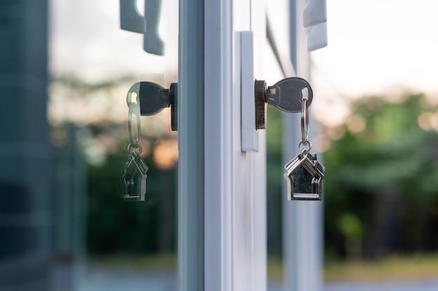 La chiave di casa per la nuova casa è inserita nella porta. la chiave è inserita nel pomello l'idea di affittare, comprare o vendere case