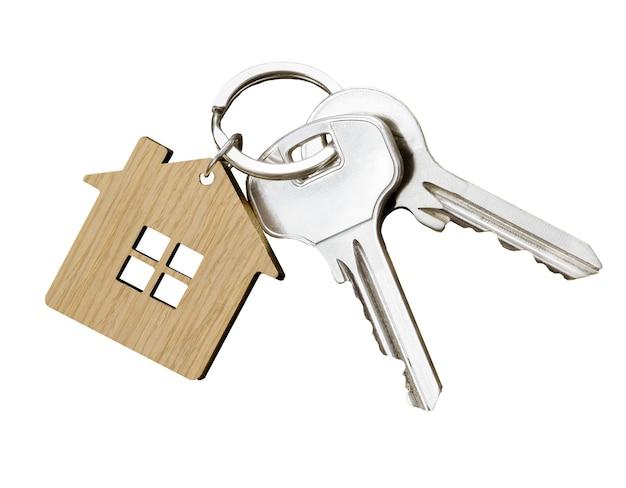 Coppia di chiavi di casa con portachiavi a forma di casa isolato su sfondo bianco. vista dall'alto.
