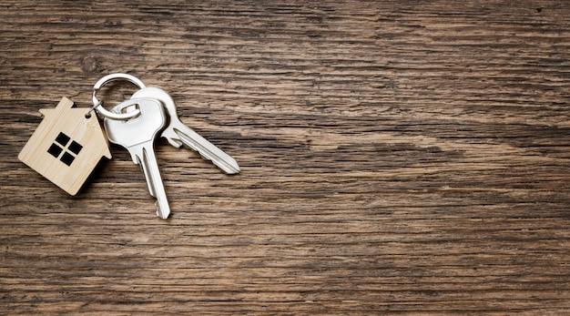Coppia di chiavi di casa con portachiavi a forma di casa su fondo strutturato in legno vecchio. vista dall'alto. copia spazio