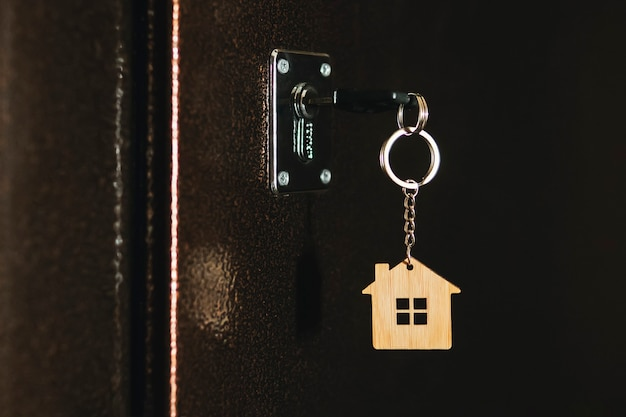 Chiave di casa con portachiavi modello casa in una porta. processo di apertura della porta d'ingresso dell'appartamento.