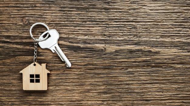 Chiave di casa con portachiavi a forma di casa su fondo strutturato in legno vecchio. vista dall'alto. copia spazio