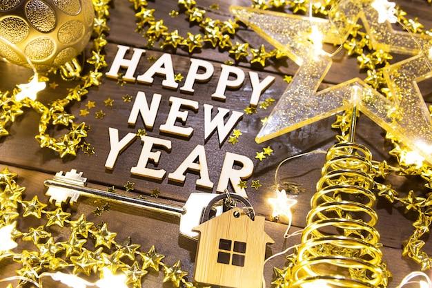 Chiave di casa con cottage portachiavi su sfondo festivo con paillettes, stelle, luci di ghirlande. felice anno nuovo in legno lettere, saluti, biglietto di auguri. acquisto, costruzione, trasferimento, mutuo