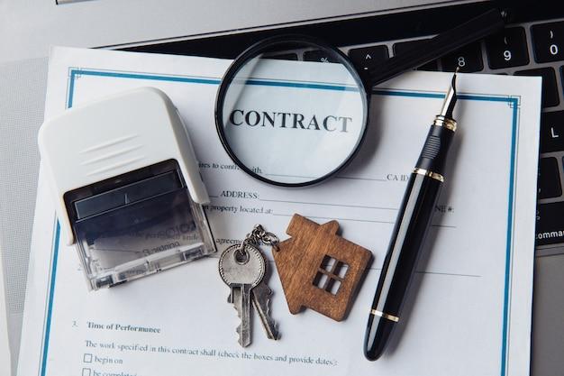 Chiavi di casa, lente d'ingrandimento e contratto. concetto di affitto, ricerca o casa ipotecaria