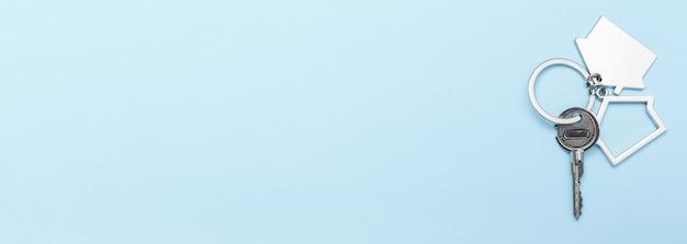 Chiavi di casa con gingillo su sfondo colorato, vista dall'alto con spazio di copia.